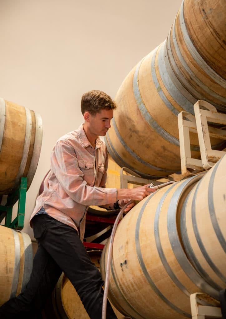 Neal Kennedy, SAMsARA Cellar Master, tops off barrels at the SAMsARA winery.